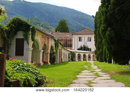 Lienz, Austria - July 16, 2014. Courtyard of Stadtpfarrkirche St. Andra in Lienz, with footpath, graves and trees