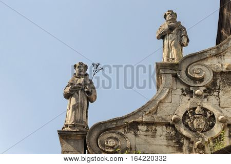 Two sculptures of monks on the roof of the catholic Bernardine church in Lviv (Lvov) Ukraine