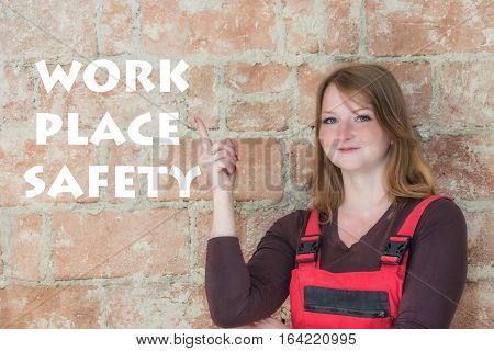 Young redhead woman dressed in red overall is standing in front of an old brick wall. Woman is looking at the camera and is pointing the finger at the sign Work Place Safety.