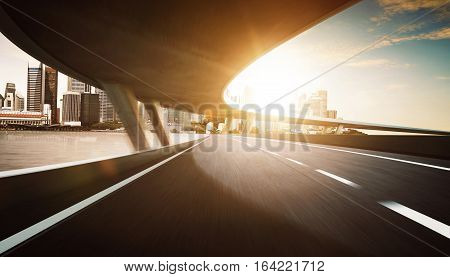 Highway and bridge overpass motion blur with city skyline background .