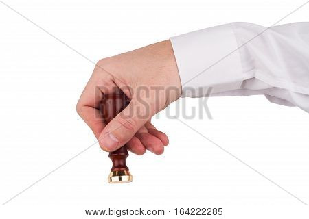 front view of male hand with white shirt holding and using a personal stamp tool with wooden handle and metallic empty head isolated on white