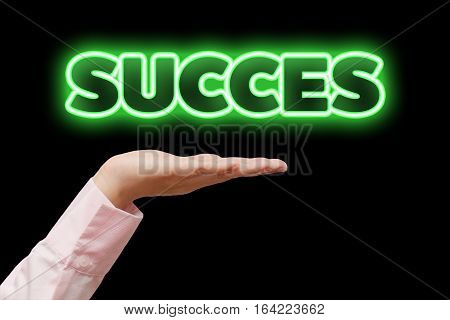 Business woman hand cupped holding the word SUCCESS with green neon light