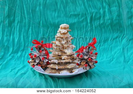 In the picture made by hand from the gingerbread Christmas tree is drenched with melted white chocolate. Next to it are two pine cones decorated with red beads and bows.