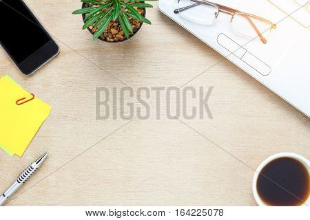 Top view accessories office desk the mobile phone note paper coffee cactus laptop on wooden office desk background.
