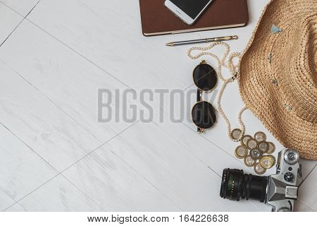 Female Travel Style Concept. Money, Jewelry, Phone, Hat, Sunglasses, Camera On White Wooden Backgrou