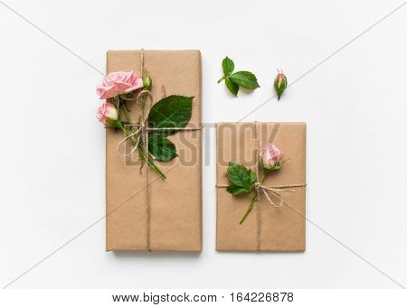 Vintage gift boxes in eco paper on white background. Presents decorated with rose flowers and leaves. Valentine's day or other holiday concept top view flat lay overhead view