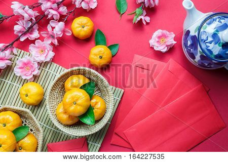 Top view accessories Chinese new year festival decorations.orange leaf wood basket red packet plum blossom teapot on red background.