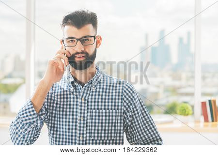 Close up portrait of handsome european boy in casual shirt and glasses talking on cellular phone. Blurry city background