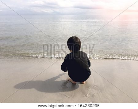 4 years old black hair Asian boy sand writing lonely on beach with sea and sky background with flare