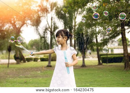 7 years old black hair in white dress play and blowing bubble balloon in park with flare and vintage tone