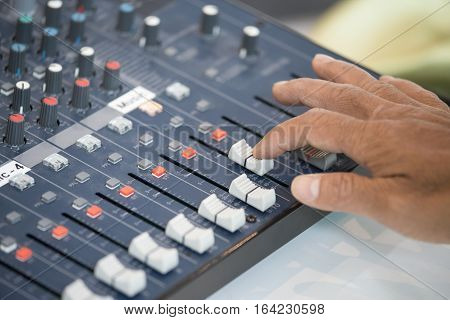 human finger slide and addjust sound on audio mixing console board