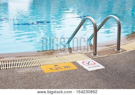 ladder and warning with depth sign for safety at swimmimg pool edge with copy space