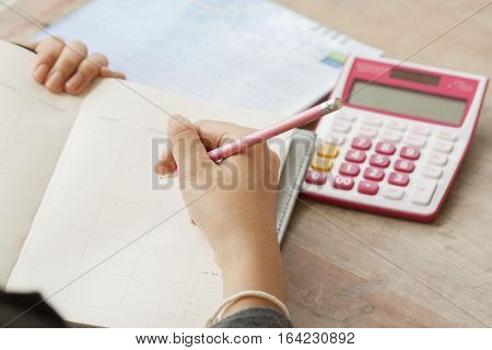 woman writing notebook planner record for financial