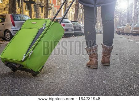 Girl tourist with luggage walking on a city street