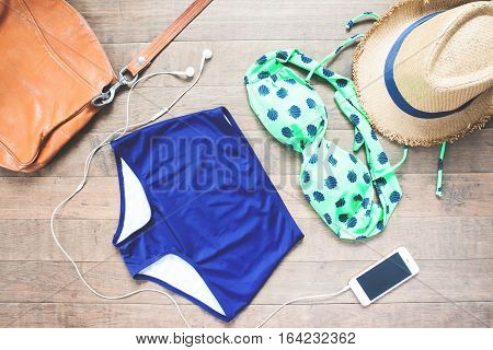 vacation travel tourism technology and objects concept - close up of smartphone and beach stuff flat lay on wood