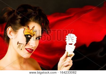 green energy fossil fuel concept: young woman holding a lightbulb, the make-up on her face shows a flame, oil and a drilling rig.