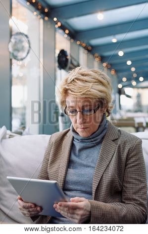 Mid age woman with tablet sitting at indoor cafe looking for screen