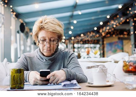 Mid age woman with mobile phone sitting at indoor cafe looking for screen