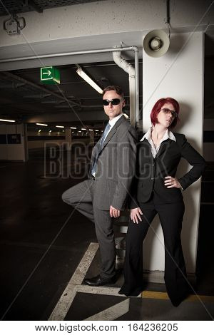 mafiosi couple posing in a parking garage