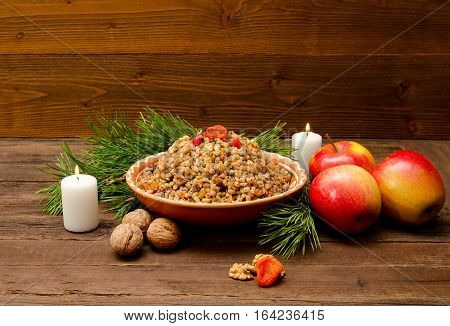 Dish with kutia - traditional Christmas treat of the Slavs on Christmas Eve. Fur-tree branch apple candle on a wooden background.