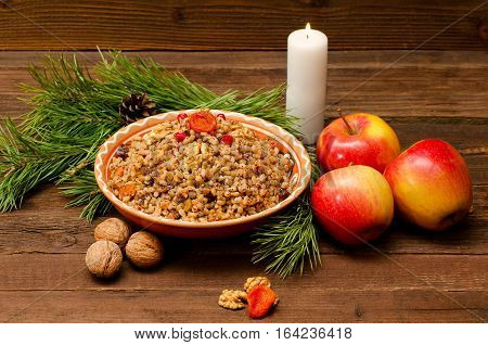Boiled wheat - a traditional Christmas treat of the Slavs on Christmas Eve kutia. Fur-tree branch apple candle on a wooden background.