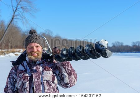 Bearded man is drilling ice hole by automatic moto boer for winter fishing at sunny day on wide river under blue sky
