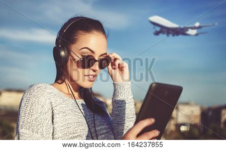 Young woman ordering air ticket by tablet on airport