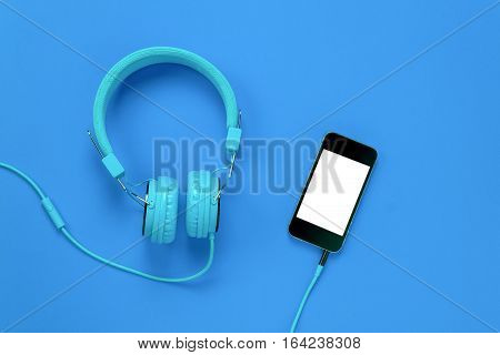 Top view mobile phone and headphones on blue background with copy space.
