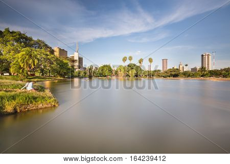 Long exposure of the skyline of Nairobi Kenya with the beautiful lake in Uhuru Park in the foreground.