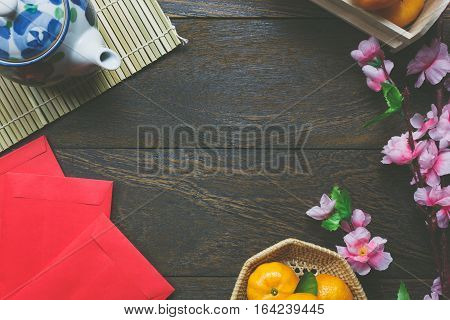 Top view accessories Chinese new year festival decorations.orange leaf wood basket red packet plum blossom teapot on wooden table background.