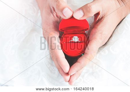 Man giving engagement ring to his girlfriend with hands heart shape. Marry me. Copy space
