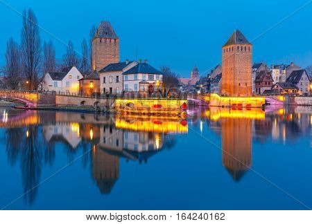 Medieval towers and bridges Ponts Couverts with mirror reflections in Petite France during twilight blue hour, Strasbourg, Alsace, France