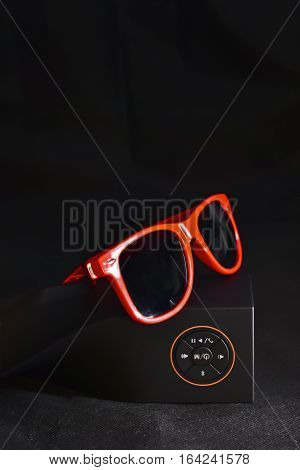 Wireless speaker with bluetooth connection on black background and glasses