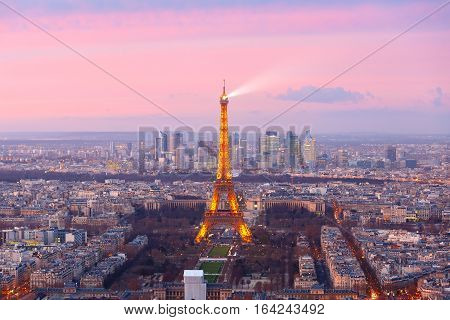 Paris, France - December 26, 2016: Aerial view of Paris skyline with Shimmering Eiffel Tower and business district of Defense at pink sunset, as seen from Montparnasse Tower