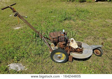 A retro unique rusty three wheeled pus lawn mower is parked and ready for usage or salvage.