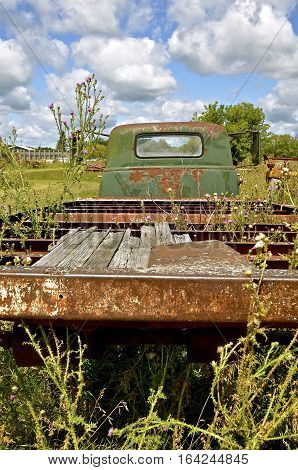Weeds are growing around a rickety old truck with boards missing in the flat bed