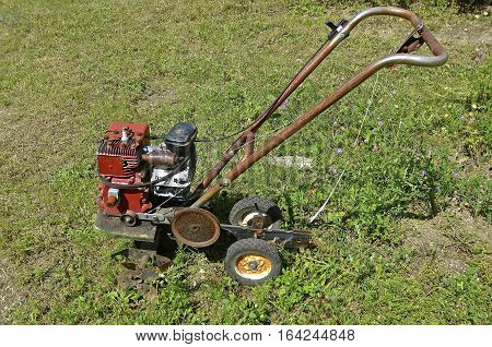 An old rusty garden tiller is ready for usage or to be sent to the junkyard for salvage,parets, or scrap metal