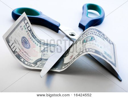 Scissors cutting through dollar note on white background