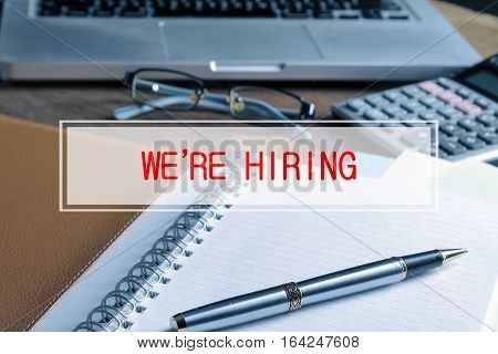 Notebook With Calculator, Keyboard And Pen On Table With Text We're Hiring