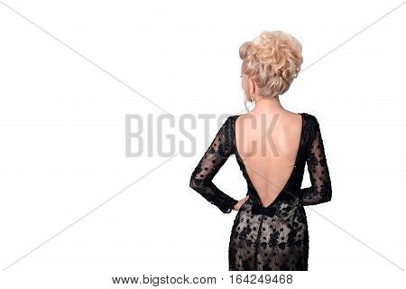 Beautiful blonde woman in elegant black evening low cut back dress with updo hairstyle. Lady looking over her shoulder on white background. Free space for text. Fashion photo for advertising something