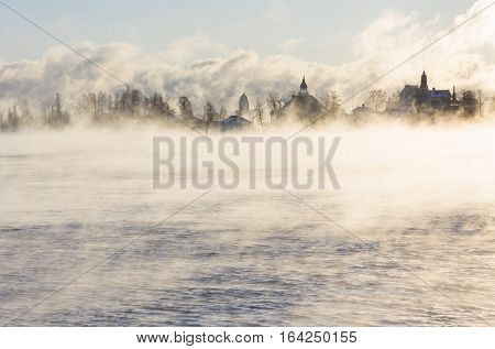 Island with buildings in a steaming ocean