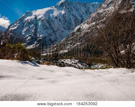 Snowy mountains in the wilderness with blue sky and sun