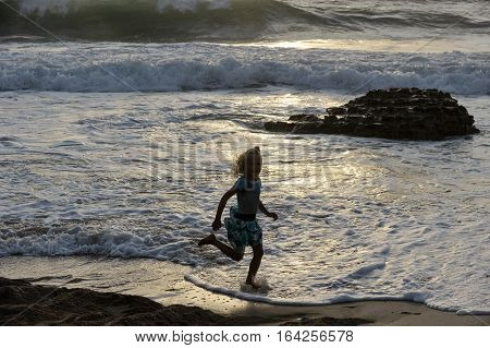 Girl runs along the shore of the Mediterranean Sea in Israel