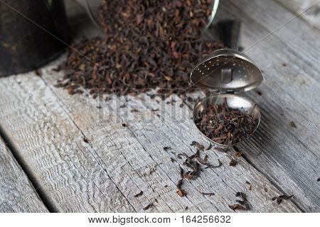 Tea brews and strainer on rustic vintage grey boards, with copy space