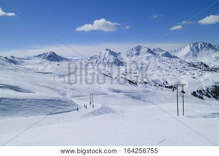 Snowboarding and skiing on fresh snow slopes in an alpine valley Paradiski Plagne Alps France