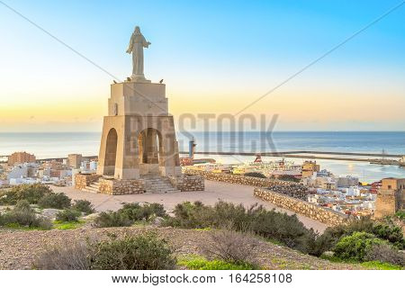 Statue of Christ staying on the hill above the Almeria city on sunrise Andalusia Spain