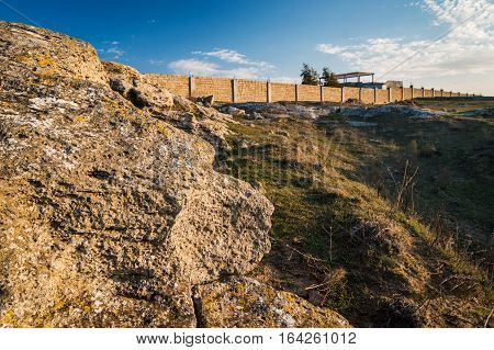 Clumps of natural limestone, the border wall in the background