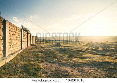 Sunrise on the border line, a fence made of limestone