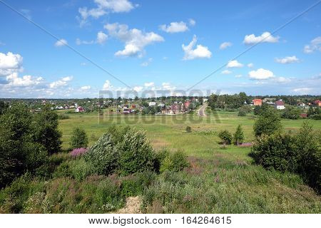 Beautiful countryside rural landscape with homes on hills far away on hot sunny summer day