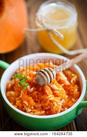 boiled pumpkin with rice and honey on a wooden table